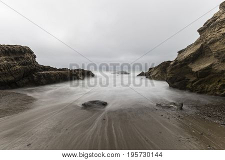 Rocky cove with motion blurred water at Leo Carrillo State Beach in Malibu, California.