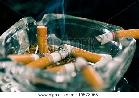 Close up of consumed cigarettes over a crystal ashtray in black background.