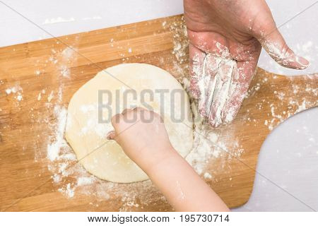 Children and dad hands rolled dough with a rolling pin on the wooden board