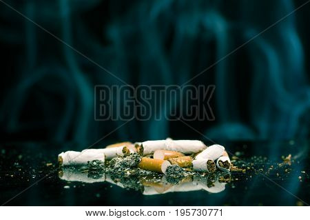 Consumed cigarettes with ash in a black background.
