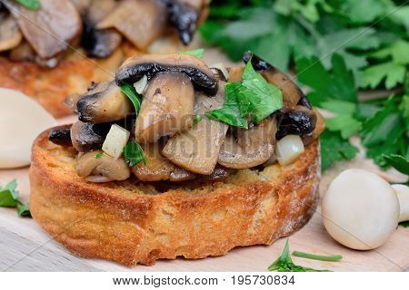 Bruschetta with mushroom and parsley on table