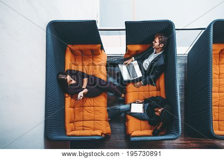 Group of business people relaxing during break while sitting on couches: afro american girl with digital tablet with blank screen mock-up caucasian man in formal suit with laptop and caucasian woman