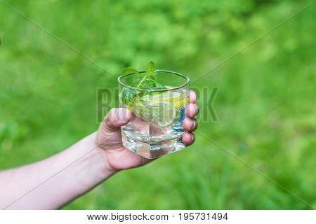 Man holding a glass of water on nature background.