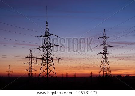 High voltage electricity pylons sunset. Electric pole power lines and wires.