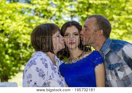 Parents kiss their adult daughter in both cheeks.