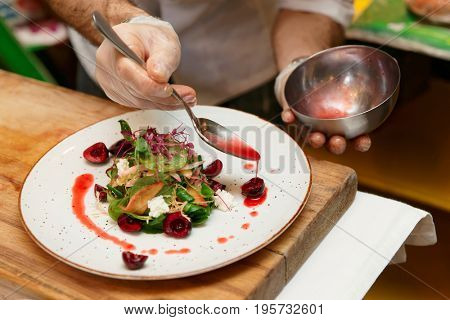 Chef is adding red sauce to vegetable and berry appetizer