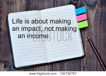Life is abot making an impact not making an income on notebook page