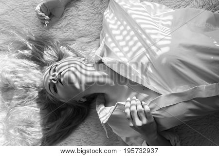 sensual girl lying on fur in sunlight with blinds, monochrome