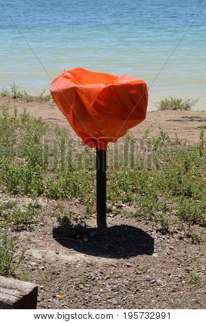 Fire ban alert and prevention with orange plastic covering outdoor cooking grills at park