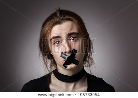 sad girl with tape on her mouth looking at camera at gray background