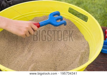 Closeup Of Boy's Hand About To Rake Sand In A Round Yellow Sandbox