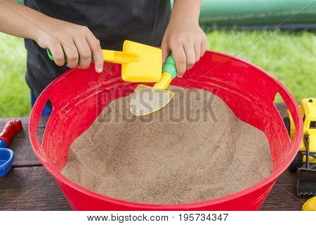 Closeup Of Boy Playing In Small Sandbox With Shovels And Scoops