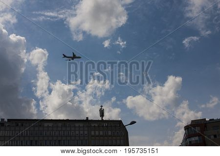 Airplane flying over buildings against a blue sky