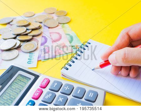 abstract money saving. Closed up woman hand using calculator with note book and red pencil in yellow background.