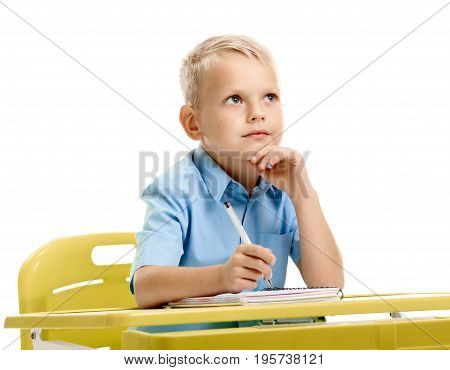 Cute minded male pupil sitting at the desk and dreaming
