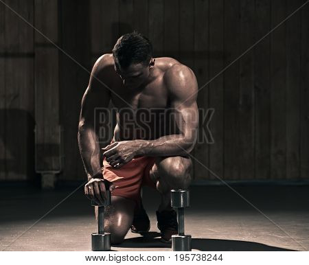 Young sportsman preparing to do push up with dumbbells in the gym, the image was desaturated ang toned
