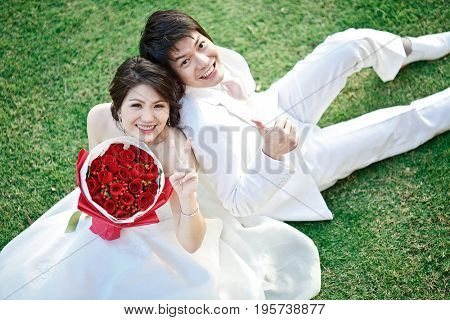 portrait of bride and groom sitting on fresh grass with rose bouquet