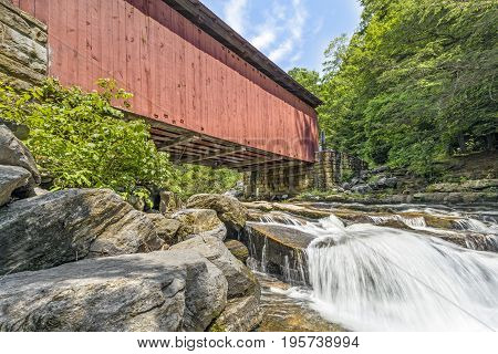 Built in 1887 the historic Packsaddle Covered Bridge crosses over a waterfall on Brush Creek in rural Somerset County Pennsylvania.