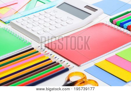 School accessories, books and fresh apple against white background