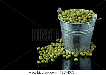 Mung beans in bucket, green  bean on  black  background.
