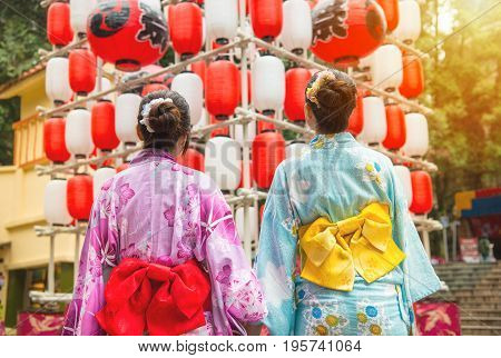 Back view of girlfriends looking up at lantern in Japanese festival. Japanese women wearing japan traditional kimono enjoying view of art decoration during travel.