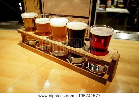 Beer samplers in small glasses individually placed in holes fashioned into a unique wooden tray.
