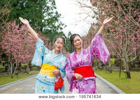 Two Women Open Arms With Cherry-blossom