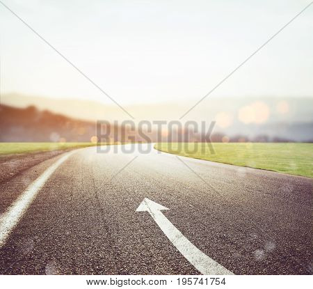 Road with arrow sign on the asphalt with sun in front. Concept