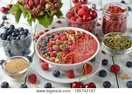 Dietary smoothies with berries in a bowl on a white background