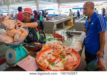 Keningau,Sabah,Malaysia-June 29,2017:Local man buy chicken meat at the local market Tamu in Keningau,Sabah.Its a place where all farmers,fishermen & vendors gathers weekly to sell their products