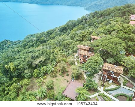 Houses in natural park near lagoon water view from drone. Lagoon Apoyo resort