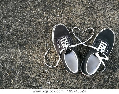 black sneaker with heart by shoelace on dark street background,concept is lover