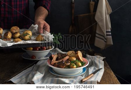 Plate with steak grilled and new fried potatoes on a rustic wooden table. Dinner table concept. Dark Style