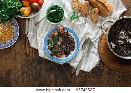 Plate with steak grilled and black quinoa on rustic wooden table top view. Dinner table concept