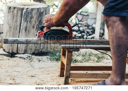 Middle aged carpenter planing the surface of a plank of wood