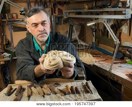 master examines wood carvings, the carpenter checks the finished work.