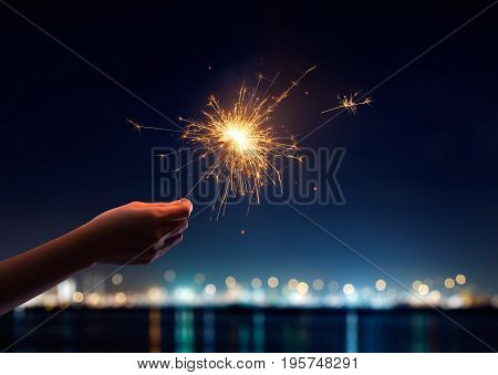 Female hand holding a burning light sparklers
