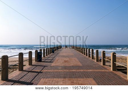 Paved patterned pier extending into ocean against blue skyline in Durban South Africa