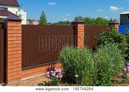 Fence made of metal profile with brick poles