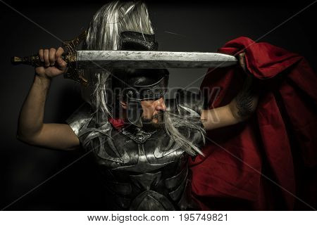 Gladiator, Roman centurion with armor and helmet with white chalk, steel sword and long red cape
