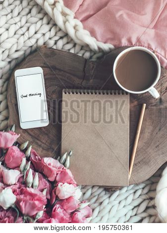 Wooden tray with paper sketchbook, smartphone and spring flowers on pink bedding. Relaxing, or working, or writing diary or blog in bed at home.