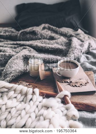 Cup of coffee and candle on rustic wooden serving tray in the cozy bed with blanket. Knitting warm woolen sweater in the autumn weekend.