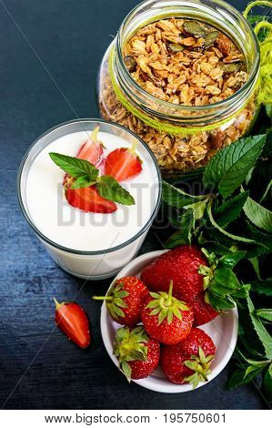 A set of a product for a delicious healthy breakfast: granola yogurt fresh strawberries green mint leaves on a black background. Proper nutrition. Dietary menu. Vertical view.
