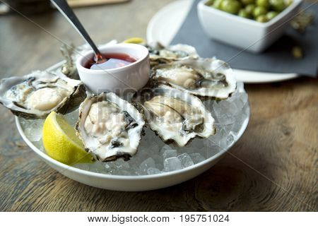 Tasty fresh oysters on ice with sliced juicy lemon on plate