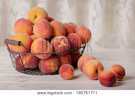 Ripe tasty peaches in a basket on a light wooden background. Selective focus.