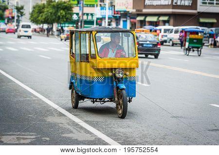HUNCHUN CHINA - September 04 2013: Auto rickshaw on the city road.