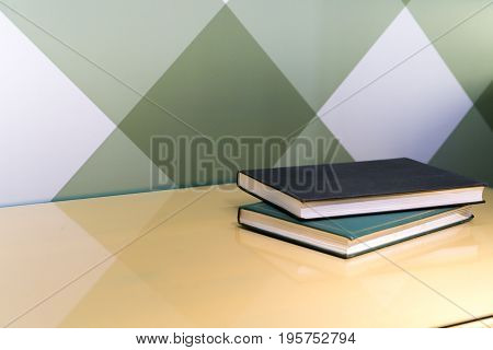 two diary book on the table near graphic wall