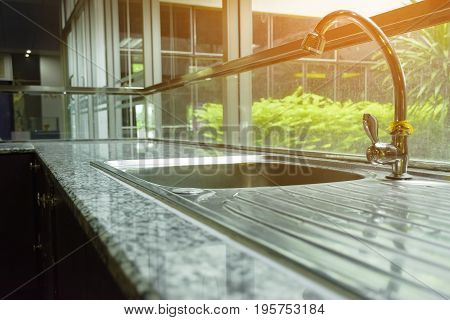 Faucet   in modern house with sunshine from garden.
