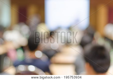 Blur background of people sitting in seminar or big meeting room with bokeh chairs tables and white slide screen to be used for business training or seminar promotion / advertising