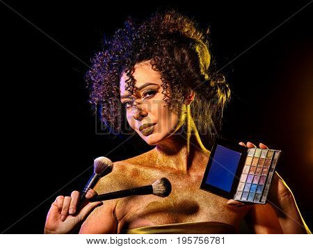 Woman with decorative cosmetics. Girl with curly hair holds eye shadow box and brush on dark background. Portrait of golden powder on female bare shoulders. Professional make-up artist.